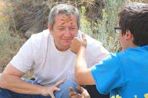 Boy painting fathers face in wilderness therapy