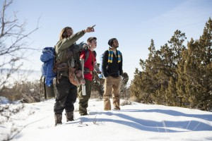 Snowy field with 3 wilderness teens and field guides pointing off in the distance