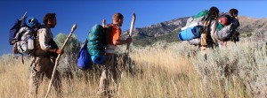 Troubled teens at a wilderness therapy hiking with hiking sticks through sagebrush
