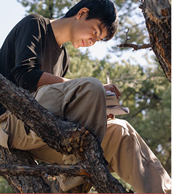 Boy sitting in a tree working on a wilderness therapy assignment