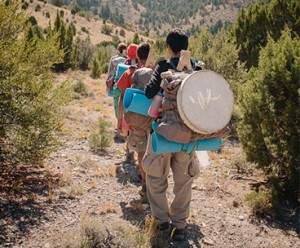 Hiking trail full of wilderness teens walking with their full packs of wilderness gear and skills
