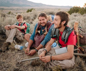 Youth boys sitting in the wilderness during a therapy session