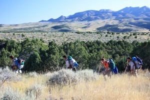 Four Wilderness therapy teens hiking through sagebrush with juniper trees and blue mountains in the distance