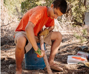 A wilderness youth cutting a piece of wood to make a wilderness skill