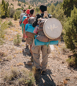 A line of wilderness teens hiking with their full packs of wilderness gear and skills