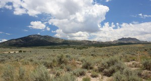 Open view of the field at Outback Therapeutic Expeditions with sagebrush, mountains and white clouds