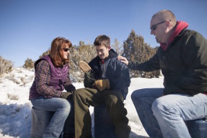 Teen boys and parents in desert in the snow