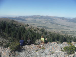 three boys top of mountain after hike in Utah wilderness