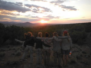 Group of troubled teen girls watching sunset in wilderness therapy