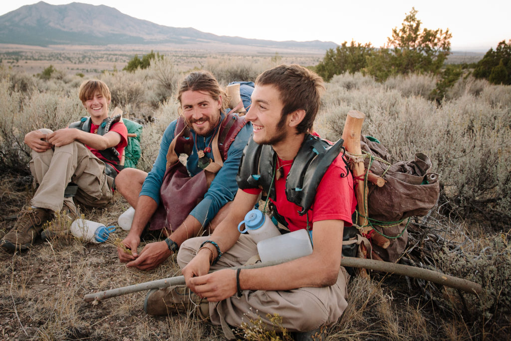 Group sitting down wearing hiking packs in wilderness therapy