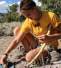 wilderness teen girl in yellow shirt making fire with bow drill