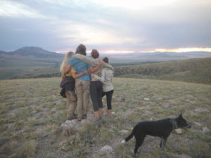 Group of four girls in wilderness therapy looking over a mountain with a dog in the foreground