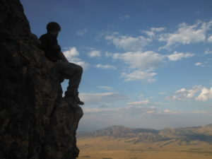 Wilderness therapy teen sitting on mountain looking over valley