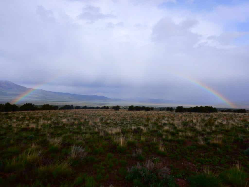 A rainbow shines over a field at Outback Therapeutic Expeditions